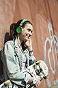 Smiling teenage girl with skateboard hearing music - UUF000181