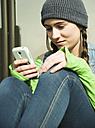 Portrait of smiling teenage girl using smartphone - UUF000196