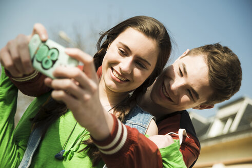 Portrait of teenage couple photographing themselves with smartphone - UUF000203