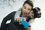 Portrait of teenage couple photographing themselves with smartphone - UUF000215