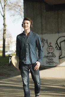 Teenager with skateboard hearing music - UUF000168