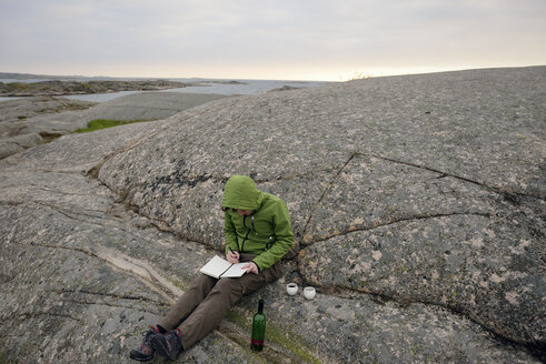 Sweden, Kungshamn, Young man at skerry coast writing in diary - BR000214