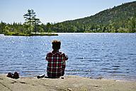 Sweden, Oernskoeldsvik, Man sitting at lake Taernaettvattnen in Skuleskogen National Park - BR000378