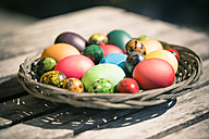 Germany, Colorful Easter eggs on wooden table - SARF000457