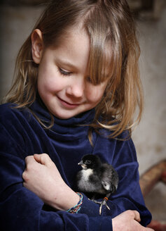 Portrait of little girl holding baby chicken - SLF000379