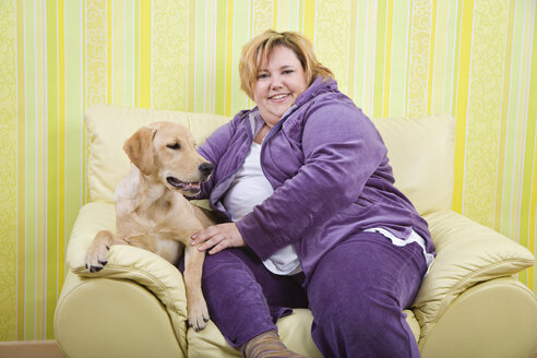 Germany, Mid-adult woman with dog sitting in arm chair - ECF000602