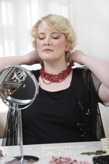 Blond woman putting on necklace - ECF000537