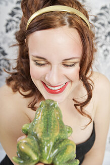 Portrait of smiling young woman kissing frog - ECF000525