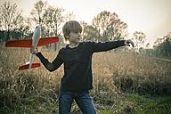 Germany, Bavaria, Landshut, Boy playing with toy aeroplane - SARF000476