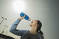 Young woman drinking water from bottle - UUF000310