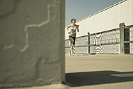 Young woman with headphones jogging - UUF000229