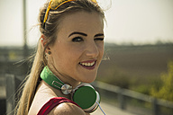 Smiling blond young woman with headphones - UUF000232