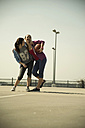 Two young women with basketball outdoors - UUF000241