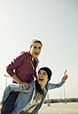 Happy young woman carrying friend piggyback - UUF000244
