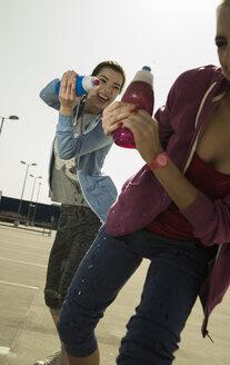 Two playful young women splashing with water bottle - UUF000249