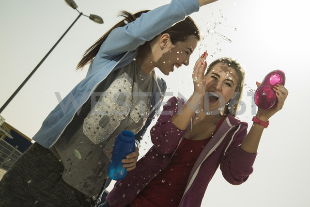 Two playful young women splashing with water bottle - UUF000251 - Uwe Umstätter/Westend61