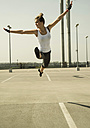 Young woman jumping mid-air on parking level - UUF000256