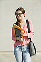 Brunette young woman with bag, folder and digital tablet outdoors - UUF000307