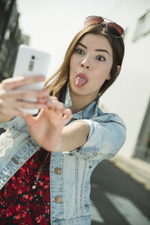 Grimacing young woman taking a selfie outdoors - UUF000273