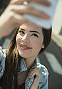 Brunette young woman taking a selfie outdoors - UUF000274