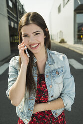 Brunette young woman using cell phone outdoors - UUF000279