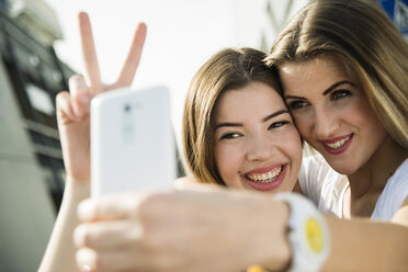 Two happy young women taking a selfie outdoors - UUF000281