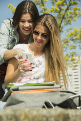 Two happy young women using cell phone outdoors - UUF000282