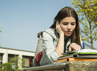 Brunette young woman lying on bench using digital tablet - UUF000300