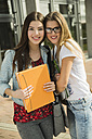 Two smiling young women with  folder outdoors - UUF000290