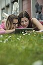 Two young women using digital tablet in meadow - UUF000297