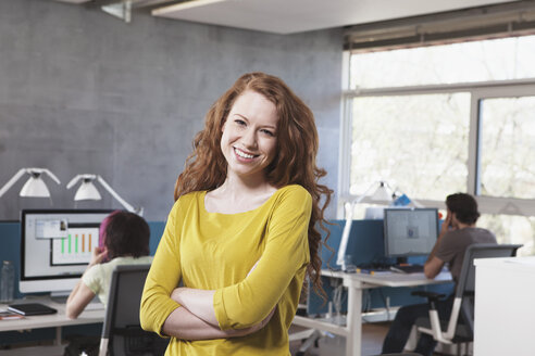 Portrait of smiling young woman in open space office - RBF001611