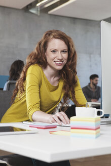 Portrait of smiling woman at her workplace in the open space office - RBF001616