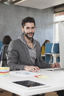 Portrait of smiling man at his workplace in the office - RBF001618