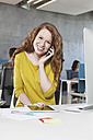 Portrait of smiling woman telephoning with smartphone at her workplace in the open space office - RBF001620