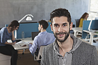 Portrait of smiling man in an open space  office - RBF001637