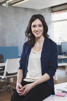 Portrait of smiling woman sitting at her workplace in the open space office - RBF001642