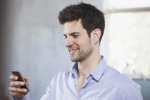 Portrait of smiling man looking at his smartphone - RBF001646