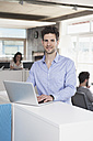 Portrait of smiling man with laptop standing in the open space office - RBF001661