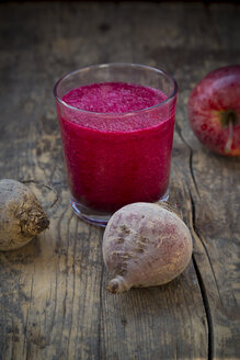 Glass of apple beetroot smoothie on dark wooden table - LVF001046