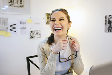 Laughing woman at modern home office - EBSF000169