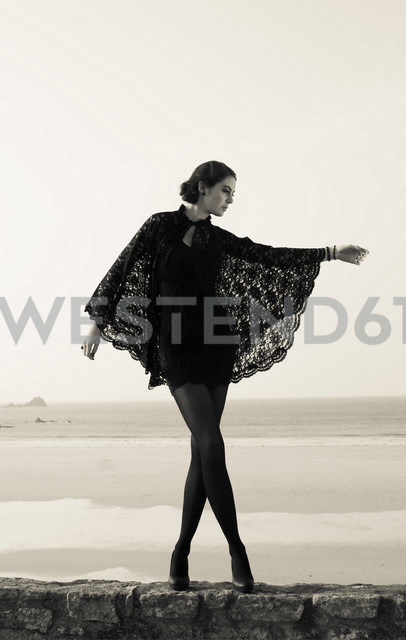 France, Bretagne, woman in black dancing on wall in front of the sea - FCF000026