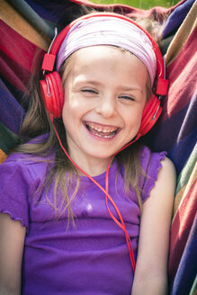 Portrait of laughing little girl with red headphones - SARF000497