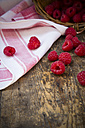 Kitchen towel and raspberries on wooden table - LVF001070