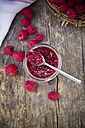 Glass of raspberry jam and raspberries on wooden table, elevated view - LVF001069