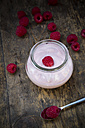 Glass of raspberry yogurt and raspberries on wooden table, elevated view - LVF001066