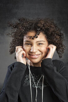 Portrait of smiling young girl listening music - ECF000603