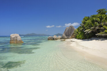 Seychelles, La Digue, view to Anse Source d' Argent with sculpted rocks and palm trees - RUEF001236
