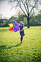 Little girl with balloons running on a meadow - SARF000487
