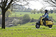 Young man driving with his Vespa on country road - LAF000730