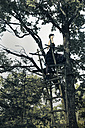 Germany, Blindfolded woman on raised hide in tree - FC000041